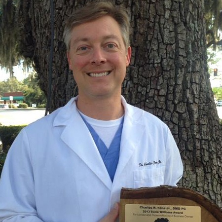 Dr. Fana smiling with plaque