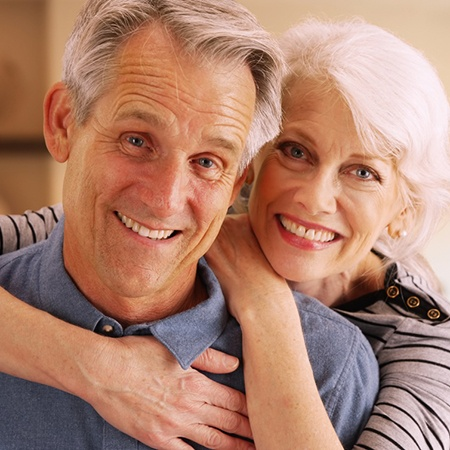 An older couple smiling and hugging in a home.