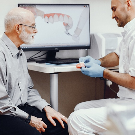 A dentist explaining All-on-4 dental implants to an older patient.