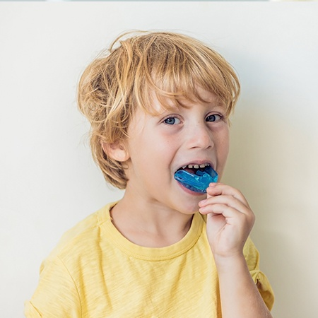 Young boy placing sports mouthguards