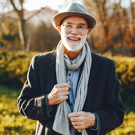 Older man with hat smiling with implant retained dentures