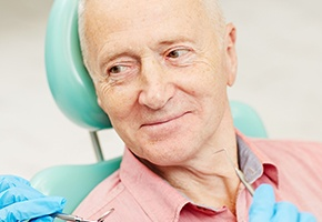 Older man in dental chair smiling