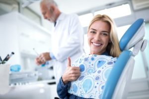 woman giving thumbs up while seeing dentist in Savannah