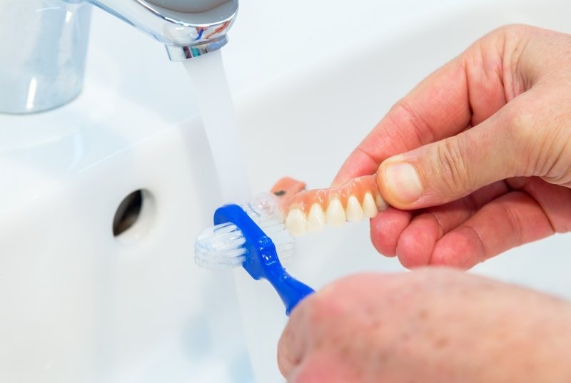 Person caring for dentures using a denture brush